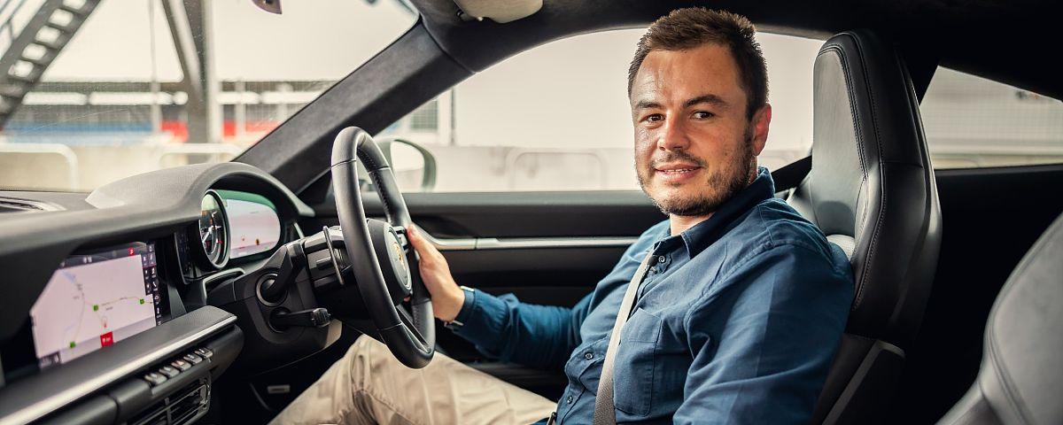 Motoring journalist Paul Maric sitting inside a Porsche 911
